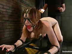 Cici Rhodes loves the dungeon. Thonged to a board, tied and gagged the brunette hair receives a punishment with sexy wax and spanking. Her master removes a metal plug from her ass, then re-inserts it, attaching a rope from it to her head. A sex-toy runs over her pussy, making her want to cum, but can't yet.