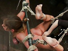 Hawt milf brunette's hands and legs are bound and suspended in nature's garb in the air. Her oily boobs are too tied. Her legs are made widened so that the girl can easily penetrate in her pussy. She put her fingers unfathomable in brunette's cunt.