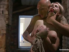 This sexy blonde babe, Isabella Clark, receives abducted by a bald guy and taken to a quiet place. Her mouth is ball gagged and she is completely naked! The guy fastened her on a bed and left her there. After a while, a guy comes in and begins teasing her with his cock and bonks her from behind