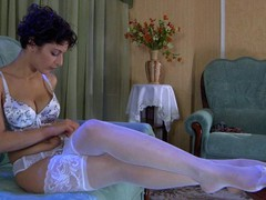 Bobbed dark brown hair lovingly smoothing her luscious white lace top stockings