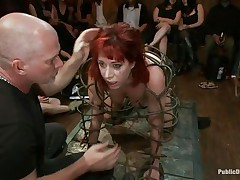 They've putted her in a special cage and as the bald dude fucks her sexy mouth, 3 dirty strumpets are taking worthy care of her ass. She is drilled from both ends and the sex toy and fingering she's getting on her wazoo only makes her mouth want to swallow that dong as deep as she can while the public see her.