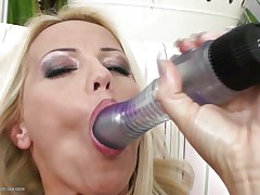 Blond milf wearing only a couple of hot black stockings is playing solo with her big dildo, that honey sucks it and the fills her hairless vagina with it, fucking herself as hard as that honey can but that is not enough. Luckily her dark brown girlfriend is willing to assist and gives her a hand, rubbing her muff and then fingering it, want to watch what else she's willing to do?