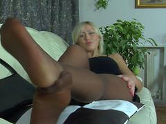 Heated blondie massaging her tasty feet right throughout her suntan pantyhose