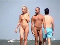 Nude pair filmed walking along the beach, precious blonde with cute whoppers and shaved pussy.