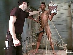 Nikki is all tied up and standing on her legs. Filled with clothespins and strings, this sweetheart has to be careful and not to drop the two buckets she`s holding, while a large vibrator makes sensations on her soaked cunt. This sweetheart acquires all whipped for being such a bad ebon girl. Her executor will take very precious care of her!
